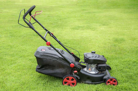 Lawn mower on green grass. mowing gardener care work tool close up view sunny day Archivio Fotografico