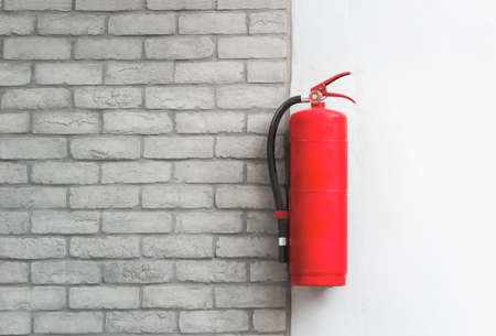 Fire extinguisher  on white brick wall background