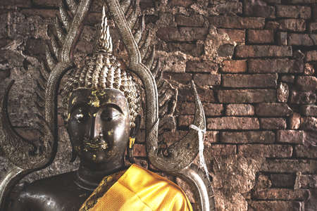 Big buddha statue at Brick wall background.