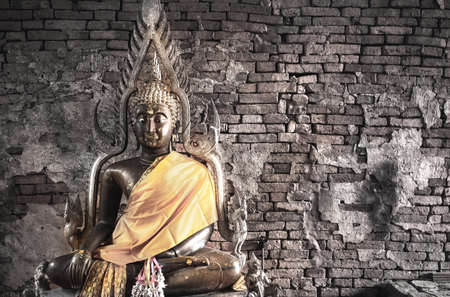 Big buddha statue at Brick wall background. Metal sculpture, Buddha statue to worship. Stock Photo