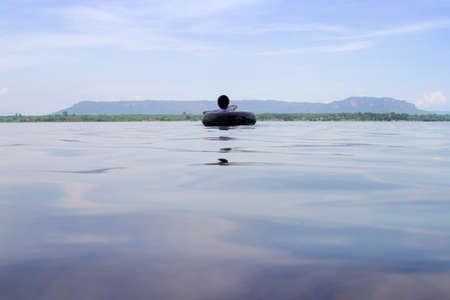 Sea surface photo with a boy lying on a rubber ring, swimming in the middle of the sea with mountains and the sky as the background.Concept of loneliness, Nostalgia