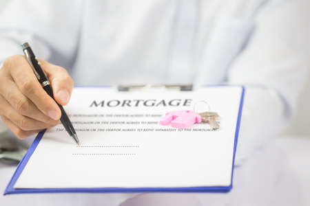 Mortgage concept. Just put your signature here! Confident young man in shirt and tie holding some document. Financial agent complete wooden model 写真素材