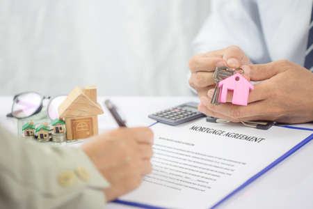 Mortgage concept. Just put your signature here! The hand of a young man holding a key  and tie holding some document. Financial agent complete wooden model