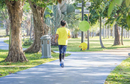 Sporty man jogging or exercise in the shady  park on early morning. Sport concept. 版權商用圖片