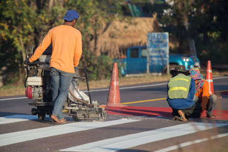 Thermoplastic spray marking machine during road construction. Worker painting white line on the street surface (Road worker painting) Banco de Imagens
