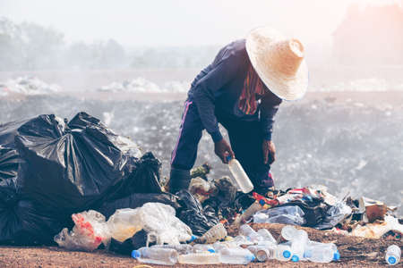 Editable of poor people scavenging recyclable trash. hand holding garbage bottle plastic putting into recycle bag for cleaning