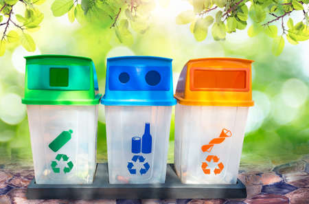 green, yellow, blue and recycle bins with recycle symbol isolated on Natural bokeh background. Concept for the environment Stock Photo