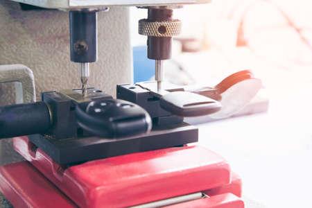 Schlosser in Werkstatt macht neuen Schlüssel. Professionelle Herstellung von Schlüssel im Schlosser. Maschinelle Herstellung von Doppelschlüsseln aus Metall.