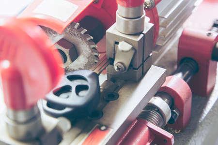 Locksmith in workshop makes new key. Professional making key in locksmith. Machine production of duplicate metal key.