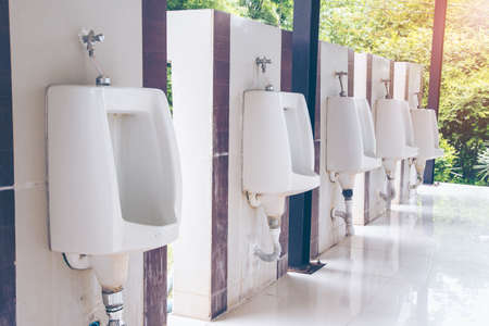 Men's room with white porcelain urinals in line. public Old bathroom. Comfort male toilet urinal concept. Foto de archivo