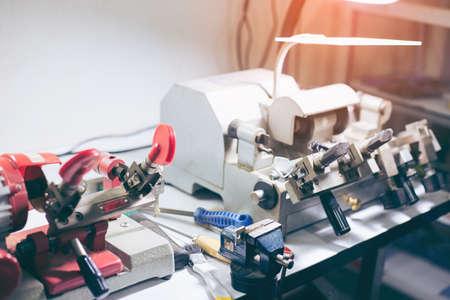 Cerrajero en taller hace nueva llave. Fabricación profesional de llaves en cerrajería. Producción a máquina de duplicado de llave metálica.