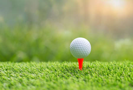 Golf ball on tee ready to be shot. putting golf ball on tee in golf course Stock Photo