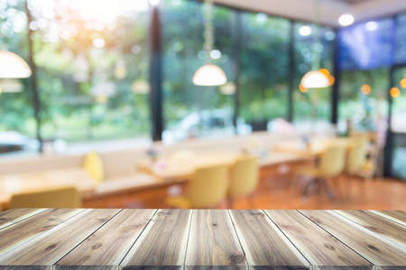 Wood table top with blur in coffee shop or (cafe,restaurant )background. For montage product display or design key visual layout Foto de archivo - 133296344