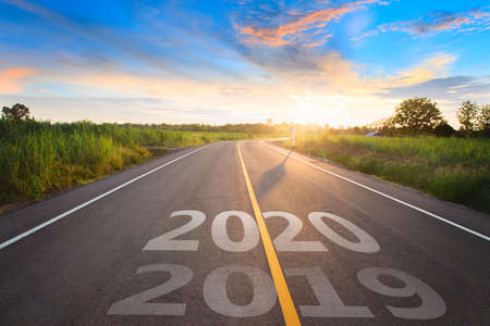 The word 2020 written on highway road in the middle of empty asphalt road at golden sunset and beautiful blue sky. Concept for new year 2020. 写真素材