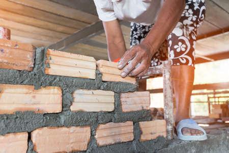 Close up of industrial bricklayer installing bricks on construction site Foto de archivo - 135082848