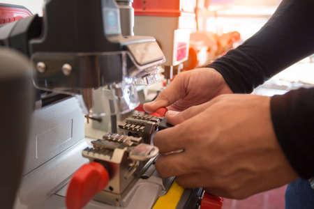 Slotenmaker in werkplaats maakt nieuwe sleutel. Professionele sleutel maken in slotenmaker. Machineproductie van dubbele metalen sleutel.