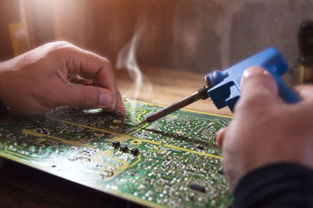 Microcircuit being fixed with soldering iron, Repair of electronic devices, tin soldering parts. Foto de archivo - 134717799