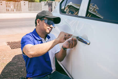 Young Man Opening White Car Door With Lockpicker. Professional making key in locksmith Stockfoto