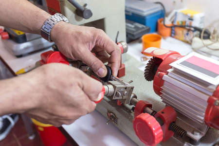Locksmith in workshop makes new key. Professional making key in locksmith. Machine production of duplicate metal key. Stockfoto