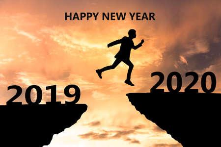 Gelukkig Nieuwjaar 2020 Silhouet. Jonge man springt over een klif in 2019 naar een klif in 2020. Tijd voor zonsondergang