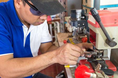 Locksmith in workshop makes new key. Professional making key in locksmith. Machine production of duplicate metal key. Foto de archivo - 135872692