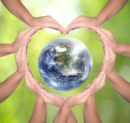 International Human Solidarity Day concept: Human hands in shape of heart. Unity, world peace, humanity concept. World environment day on Natural green background Foto de archivo - 136021510