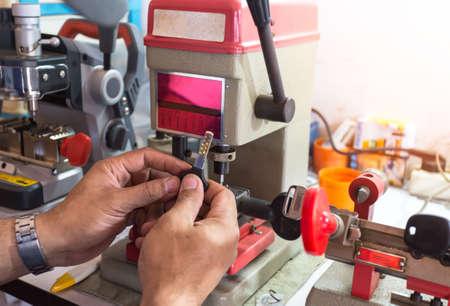 Locksmith in workshop makes new key. Professional making key in locksmith. Machine production of duplicate metal key. Foto de archivo - 136021509