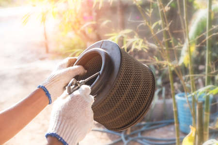 mechanic holding dirty Engine Air Filter over car and cleaning Filter with air blow gun .mechanic working in garage. Repair and maintenance car concept