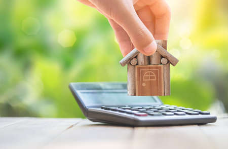 When the man who is home is put on the calculator. planning savings money of coins to buy a home concept for property, mortgage and real estate investment.to buy a house. Foto de archivo