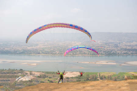 Paraglider on the ground. Paragliding flying over Landscape from Beautiful View Mekong River at Wat Pha Tak Suea in Nongkhai, Thailand. Concept of extreme sport, taking adventure/ challenge.