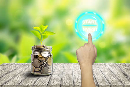 Plant Growing In Savings Coins -On finger about to press an invest button, financial concept for investment or decision making
