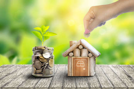 Plant Growing In Savings Coins. house and coin placed on the side. planning savings money of coins to buy a home concept for property, mortgage and real estate investment.to buy a house. Banque d'images