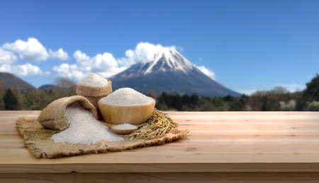 Asian uncooked white rice and burlap sack on wooden table Mount Fuji Background. rice grains healthy food, for design, advertising 免版税图像