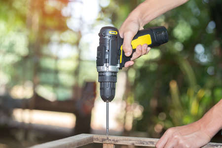 Skilled professional carpenter in workwear using electric drill machine, custom woodworking, making woodware, young experienced craftsman drilling wooden planks on table at workshop. Small business 免版税图像
