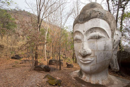 Huge sculpture of stone Buddha head on ground at Wat Umong temple of Chiang Mai, Thailand. Ruins temple in ancient time, many old abandoned damaged Buddha statue with dried leaves.
