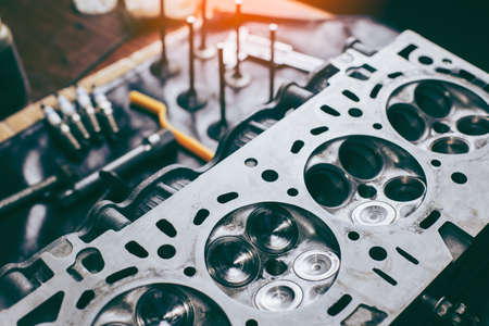 Auto mechanic working in garage. Repair service.  opened automobile engine cylinder head for maintenance repair at car service station for diagnosis