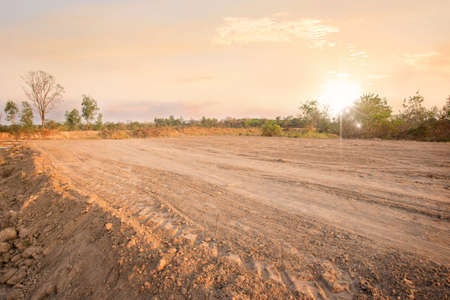 Empty dry cracked swamp reclamation soil, land plot for housing construction project with car tire print in rural area and beautiful sun set with fresh air Land for sales landscape concept