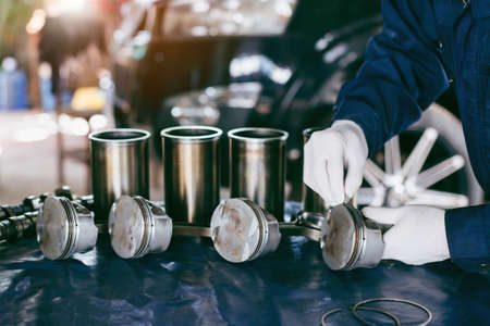 Auto mechanic working in garage. Repair service. The connecting rod, piston and cylinder block in a disassembled condition. maintenance repair at car service station for diagnosis