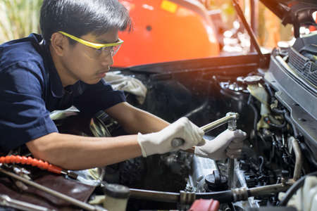 Auto mechanic working on car engine in mechanics garage. Repair service. Automotive Car repair concept