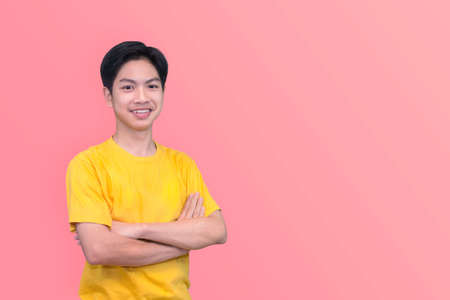 Smiling handsome Asian man in casual Yellow t-shirt with arm crossed looking at camera studio shot isolated on pink background