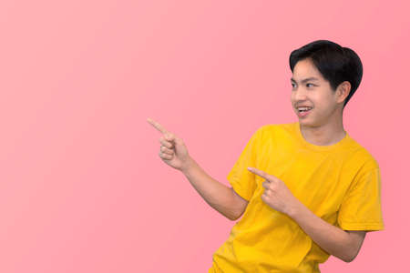 Side view portrait of smiling young handsome Asian man pointing fingers in empty space aside in isolated studio pink background 版權商用圖片