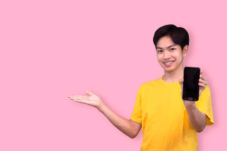 Happy smiling young Asian man showing mobile phone with another hand open on colorful pink background 版權商用圖片