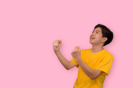 Happy excited young Asian man raising his fists doing yes gesture celebrating success in empty space aside in isolated studio pink background 版權商用圖片