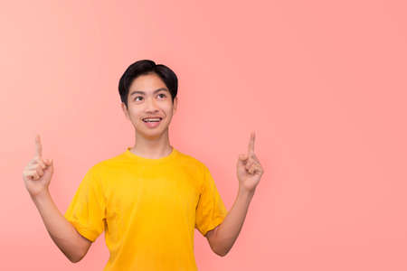 Handsome healthy young Asian man smiling with his finger pointing isolated on light pink banner background with copy space 版權商用圖片