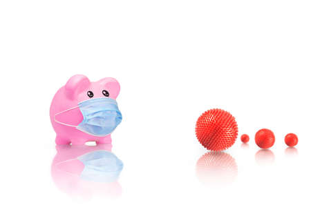 Piggy bank in medical mask with virus strain model on white background. Covid-19 pandemic. Financial difficulties due to Covid-19. Piggy bank running out of money due to coronavirus.