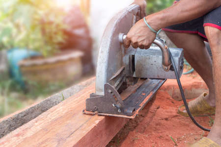Building contractor worker using hand held worm drive circular saw to cut boards on a new home constructiion project. a circular saw in the cutting a wooden plank
