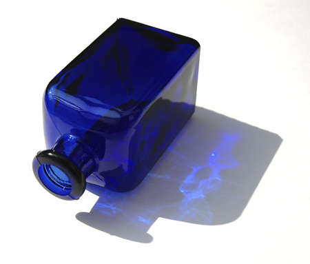 sidelit: A blue glass bottle, sunlit from the side. Stock Photo