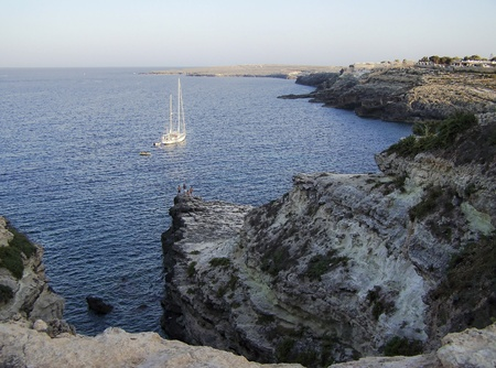lampedusa cove with fishing and boat in the distance photo