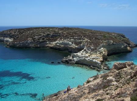 Questa è la magnifica isola dei conigli, a Lampedusa. L'acqua è cristallina e la sabbia è bianca. Le rocce si stagliano contro l'azzurro del mare e il cielo è chiaro. I fondali di questa isola sono un paradiso per i subacquei, perché sono pieni di co Archivio Fotografico - 13961178