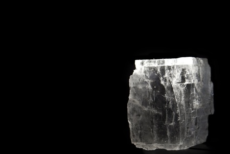 Block of rock salt mineral over black